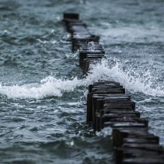 choppy water breaking over row of wood; Image via Pixabay, CC0 Public Domain