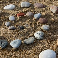 Picture of rocks in the sand in a ciruclar pattern